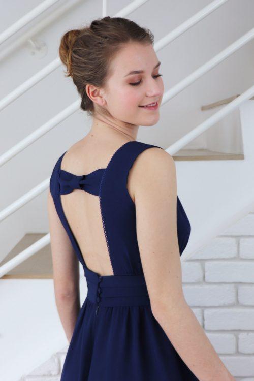 Vue de près du haut du dos de la robe de soirée bleu marine Anémone. Le noeud accroché en haut du décolleté dos apporte de l'originalité au haut du dos.
