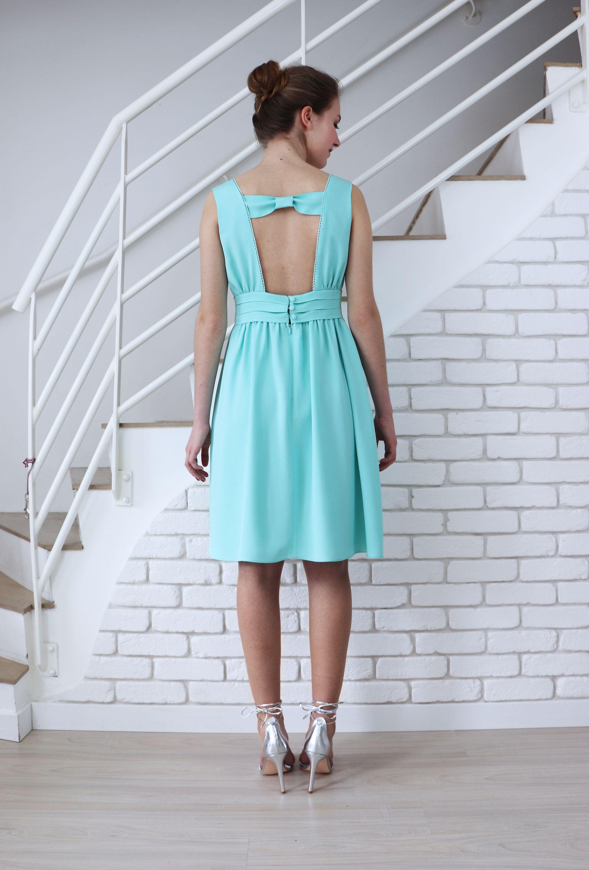 De dos, la robe de soirée Anémone dévoile un large noeud qui crée la surprise. Des petits boutons ferment la ceinture de la jupe.