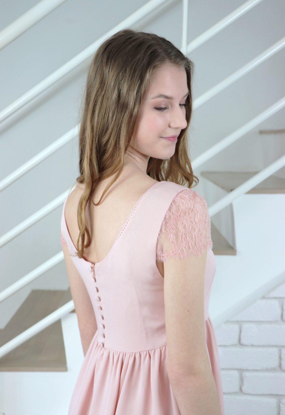 Vue de près du haut du dos de la robe de soirée rose poudré Luce. Le dos est orné de petits boutons recouverts et la manche en dentelle de Chantilly est tout en transparence.