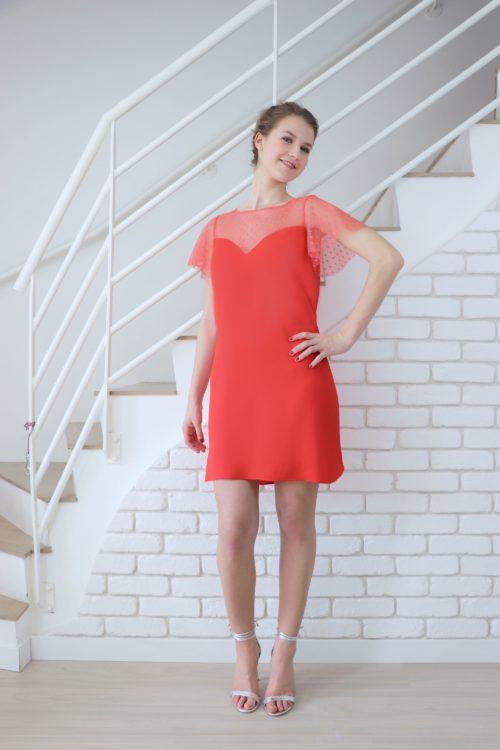 La robe de soirée rouge corail Léopoldine est fraiche et légère avec ses manches papillons en tulle plumetis ton sur ton. Son décolleté est en forme de coeur. La robe est semi ajustée et courte.
