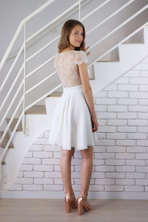 De dos, la robe de mariage civil Jeanelle crée la surprise avec son dos et ses manches entièrement recouvert de dentelle de Chantilly. La ceinture plissée ainsi que la jupe en cercle mettent en avant la taille de la future mariée.