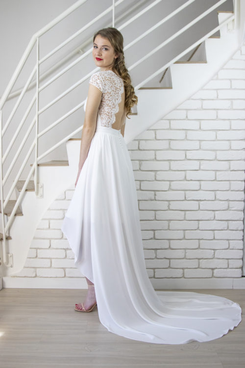 Robe de mariée Marla en dentelle de calais et mousseline. Vue de profil, l'asymétrie de la jupe apporte de la féminité à la robe.