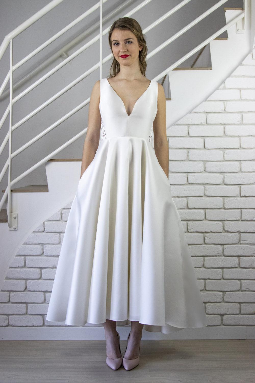 """De face, la robe de mariée Mona est élégante avec son décolleté """"v"""" travaillé, sa jupe en cercle à godets et ses poches cachées dans la couture coté de la jupe."""