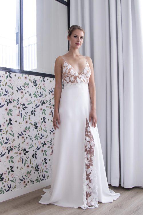 Robe de mariée Lola avec son décolleté triangle et son bas de robe fluide fendu sur la jambe et orné d'une quille en tulle rebrodé.