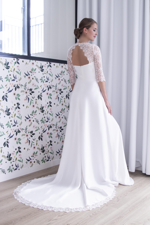 Dos de la robe de mariée Nolwen avec son dos nu en dentelle de calais et sa traine ornée d'un galon de dentelle.