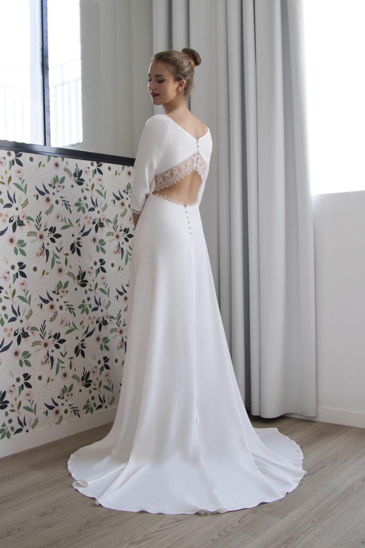 Vue de dos de la robe de mariée Carla en crèpe et dentelle de Calais. Le dos est orné de petits boutons recouverts.