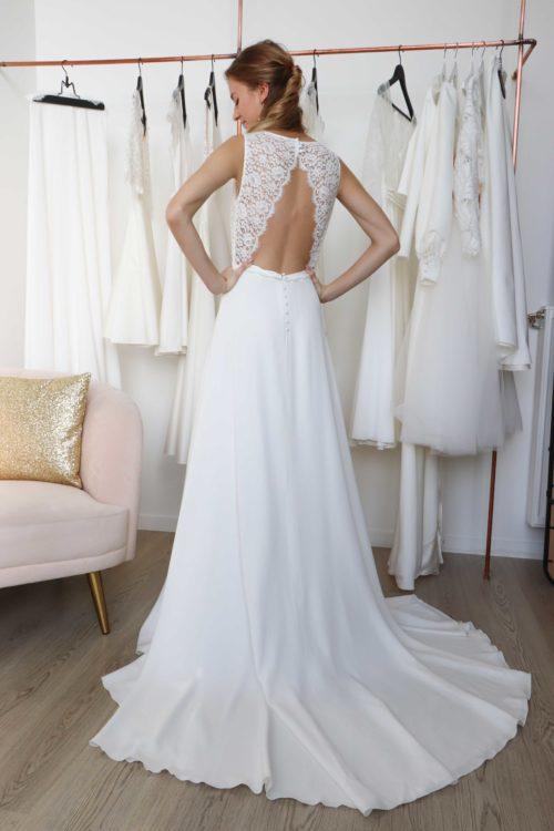 De dos, la robe de mariée en dentelle Moira est spectaculaire avec son dos nu inversé et sa grande traine.