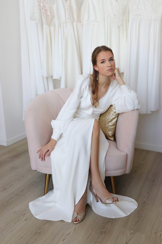 Robe de mariée Anna en crèpe, sans dentelle. Le mannequin est assis dans un fauteuil rose, une jambe se dévoile grace à la fente de la robe.